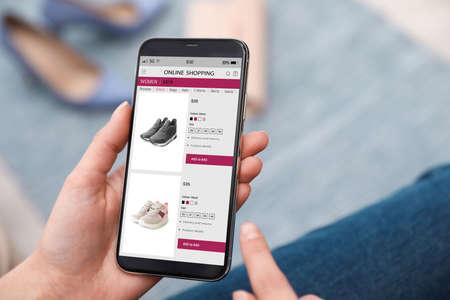 Woman shopping online via smartphone indoors, closeup