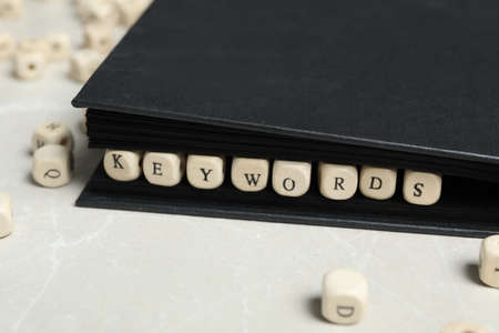 Beads with word KEYWORDS in notebook on light marble table, closeup