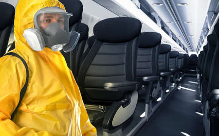 Man wearing protective suit cleaning cabin in airplane to prevent spreading of Coronavirus