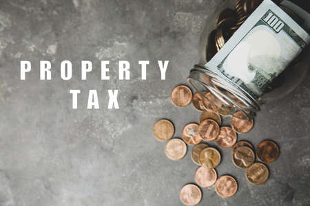 Text Property Tax near jar with dollars and coins on gray table, top view Stock fotó