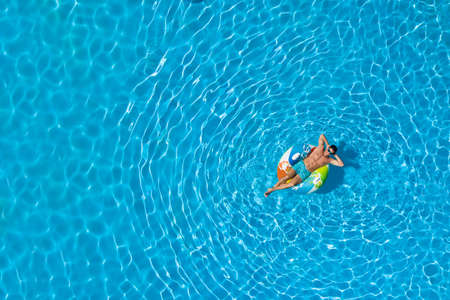 Young man with inflatable ring in swimming pool, top view. Space for text