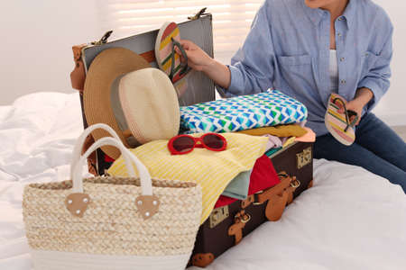 Woman packing suitcase for summer vacation in bedroom, closeup