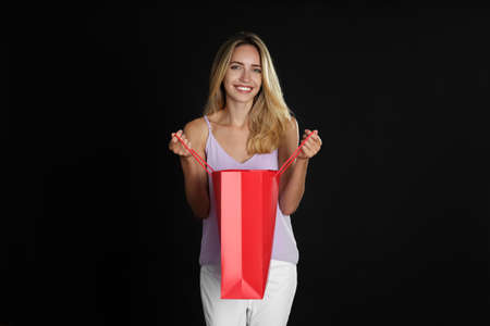 Happy young woman with shopping bag on dark background. Black Friday Sale