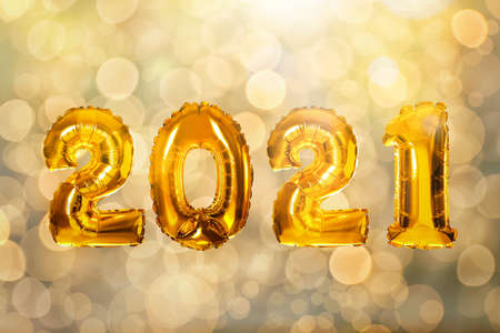 2021 New Year celebration. Bright gold balloons and blurred lights on background Stock Photo