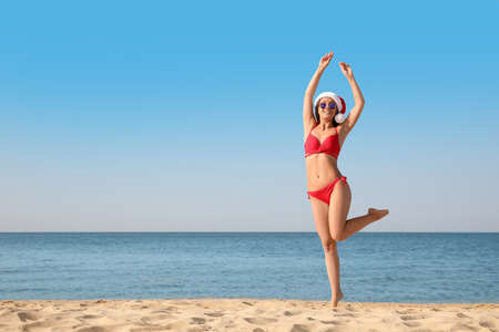 Beautiful young woman in Santa hat and bikini having fun on beach, space for text. Christmas vacation