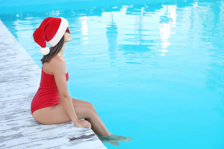Young woman wearing Santa Claus hat near swimming pool, space for text. Christmas vacation Stock Photo