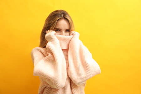 Beautiful young woman wearing knitted sweater on yellow background