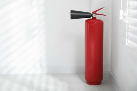 Fire extinguisher near white wall indoors. Space for text Stock fotó