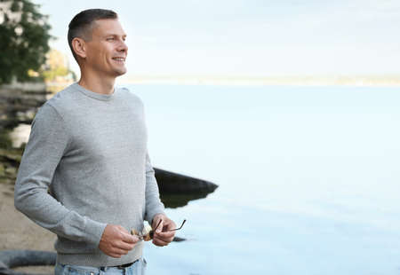 Happy man in stylish sweater on beach Stock Photo