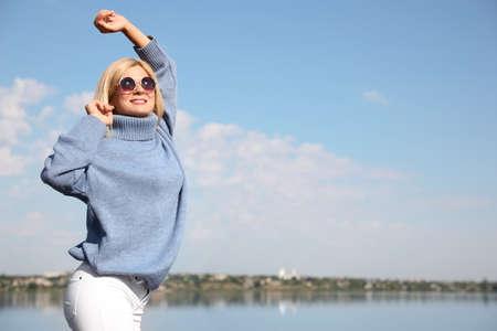 Happy woman in stylish sweater on beach Stock Photo