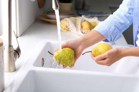 Woman washing fresh ripe pears in kitchen, closeup