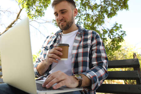 Young man with paper cup of coffee working on laptop in park
