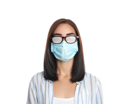 Young woman with foggy glasses caused by wearing disposable mask on white background. Protective measure during coronavirus pandemic