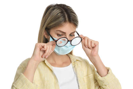 Woman wiping foggy glasses caused by wearing disposable mask on white background. Protective measure during coronavirus pandemic Фото со стока