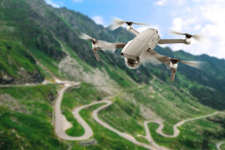 Modern drone flying over picturesque mountains. Aerial survey