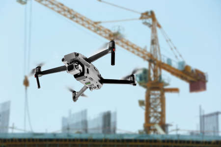 Modern drone flying at building site. Aerial survey