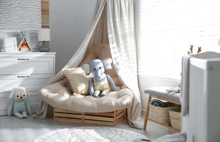 Comfortable armchair in modern baby room interior