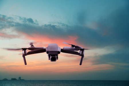 Modern drone flying over sea at sunset. Aerial survey Reklamní fotografie