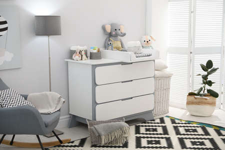 Beautiful baby room interior with modern changing table and rocking chair