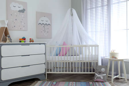 Baby room interior with cute posters, chest of drawers and comfortable crib Stock fotó