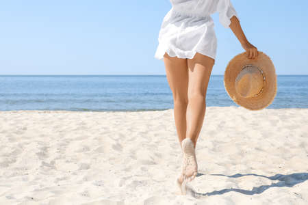 Young woman with beautiful body on beach, closeup. Space for text