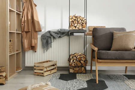 Firewood as decorative element in stylish room interior Stock Photo