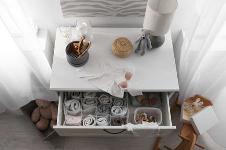 Modern open chest of drawers with baby clothes and accessories in room, above view