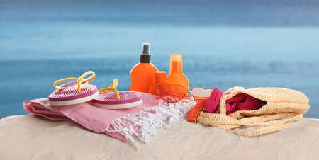 Different beach accessories on sand near sea. Banner design