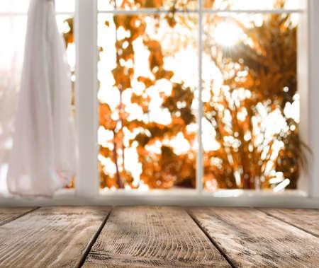 Empty wooden table near window on sunny autumn day