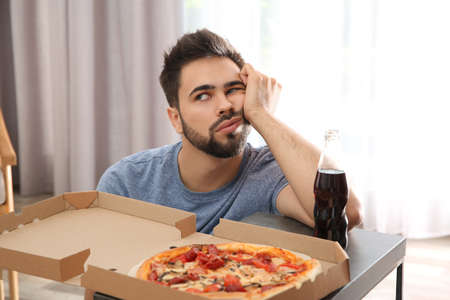 Lazy young man with pizza and drink at home Stock Photo