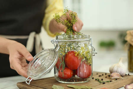Woman putting dill into pickling jar at table in kitchen, closeup Banco de Imagens
