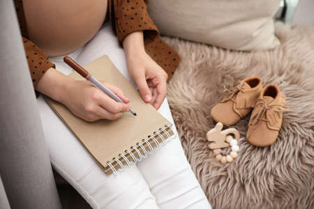 Pregnant woman writing baby names list at home, closeup