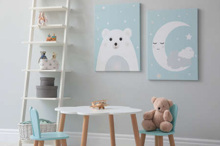 Children's room interior with table and cute pictures on wall Standard-Bild