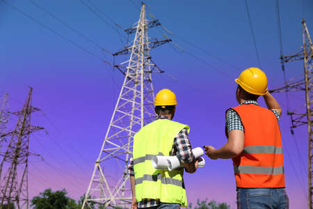 Professional electricians in uniforms near high voltage towers