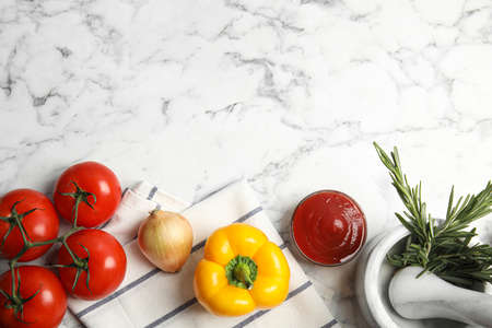 Flat lay composition with ingredients for cooking on white marble table. Space for text