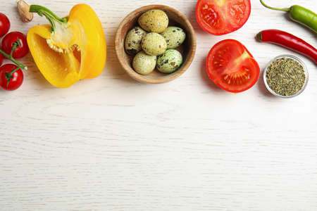 Flat lay composition with ingredients for cooking on white wooden table. Space for text