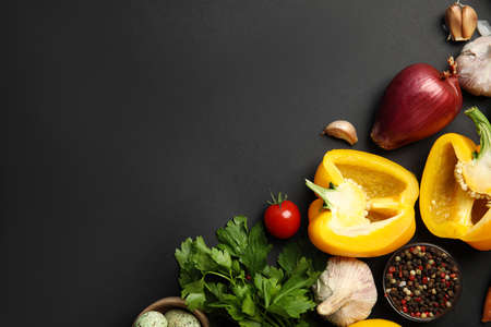 Flat lay composition with ingredients for cooking on black background. Space for text