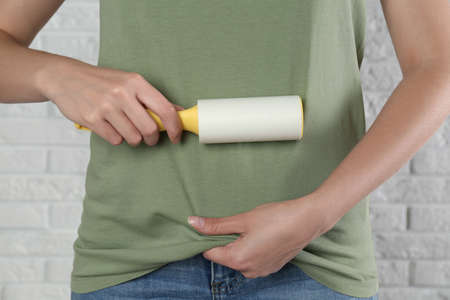 Woman cleaning green t-shirt with lint roller against white brick wall, closeup