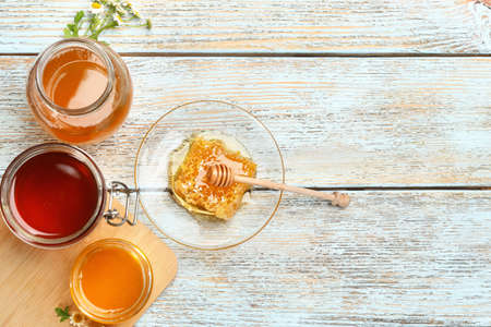 Flat lay composition with different types of honey on light blue wooden table. Space for text Фото со стока
