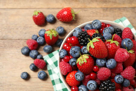 Mix of ripe berries on wooden table, flat lay