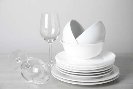 Clean plates, bowls and glasses on table against white background