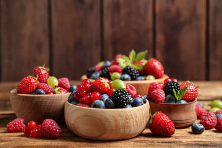 Mix of ripe berries on wooden table