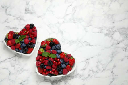 Mix of ripe berries on white marble table, flat lay. Space for text Stock fotó