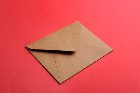 Brown paper envelope on red background. Mail service