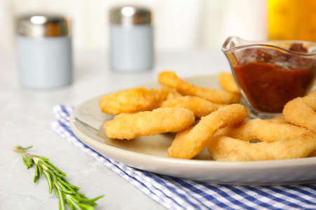 Delicious crunchy fried onion rings and rosemary on light table, closeup
