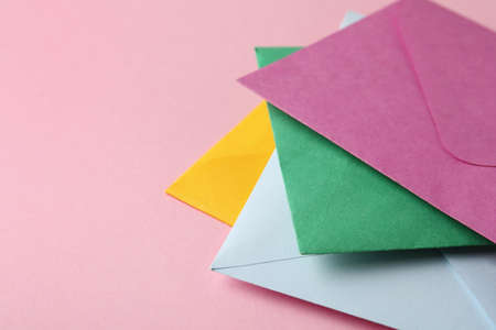 Colorful paper envelopes on pink background, closeup. Space for text