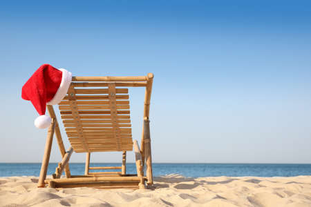 Sun lounger with Santa's hat on beach, space for text. Christmas vacation