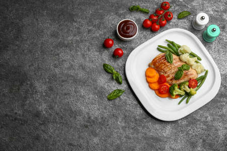 Tasty grilled chicken fillet with vegetables and sauce on gray table, flat lay. Space for text Stock fotó - 155452216