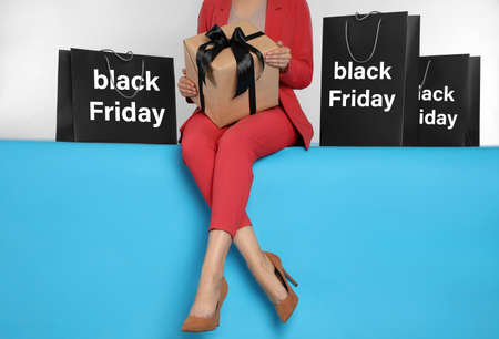 Woman with gift box and shopping bags sitting on light blue background, closeup. Black Friday