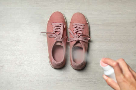 Woman spraying deodorant over pair of shoes at home, closeup